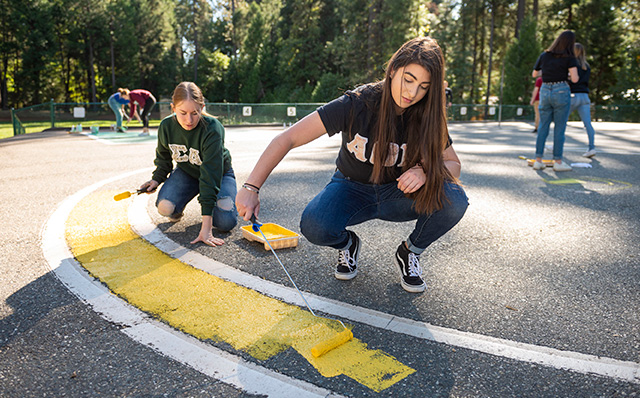 Student in the community helping paint lines on blacktop