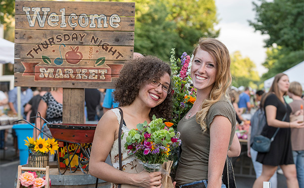 Smiling students holding bouquet of beautiful flowers at farmers market