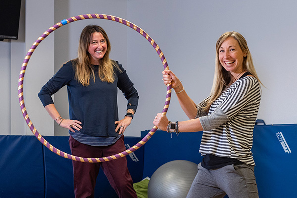 Two women smiling and one is holding a hula hoop.