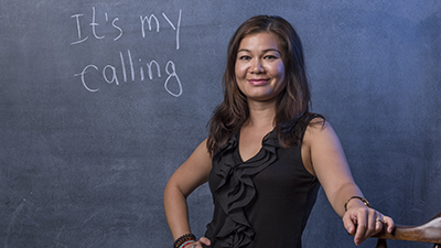 "A new faculty member writes ""it's my calling"" on a chalkboard"