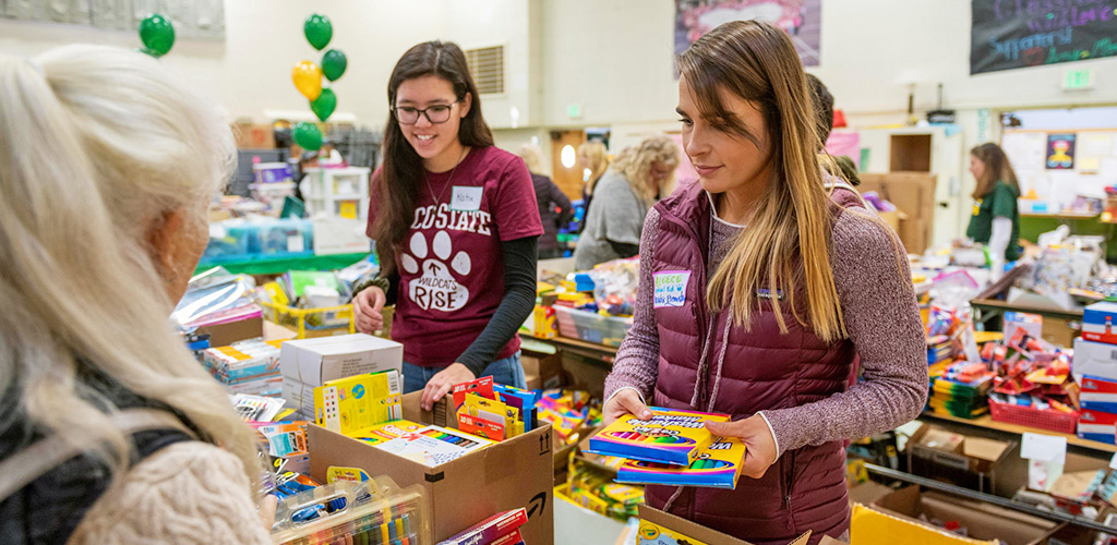 Two students organize supplies in a donation center for the Camp Fire victims
