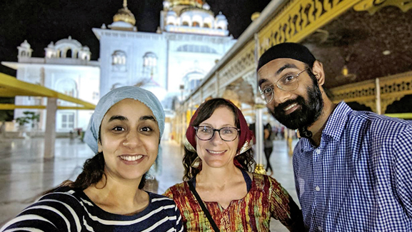 Three people stand in front off a tourest location while smiling at the camera and taking a selfie on their study abroad journey.