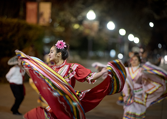 A costumed dancer swishes her colorful skirt in motion as she dances at night.