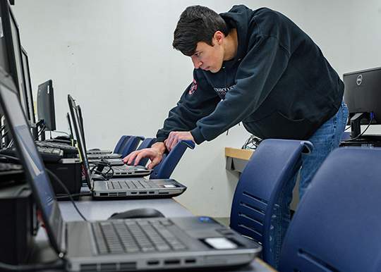 A technology worker hovers over a laptop in concentration as he moves through a line of laptops waiting to be serviced. He is between two tables holding computers arrayed in a row with empty chairs.