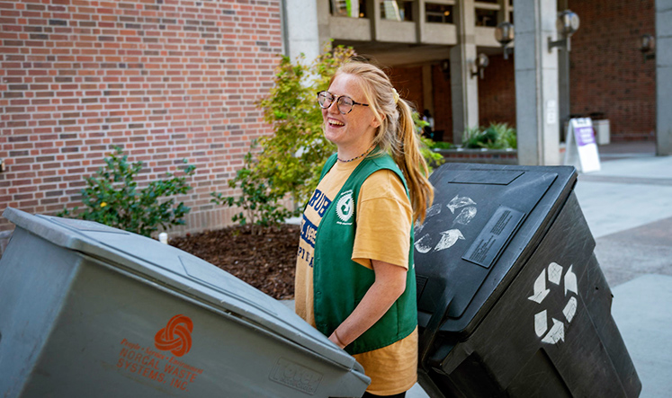 Smiling student rolls recycle bins across campus
