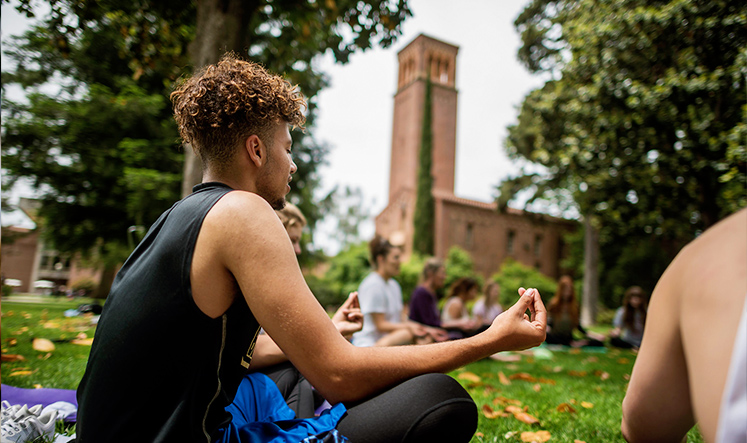 yoga class outdoor with campus bell tower in the background