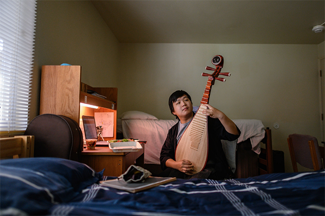 Student plays the pipa in his room